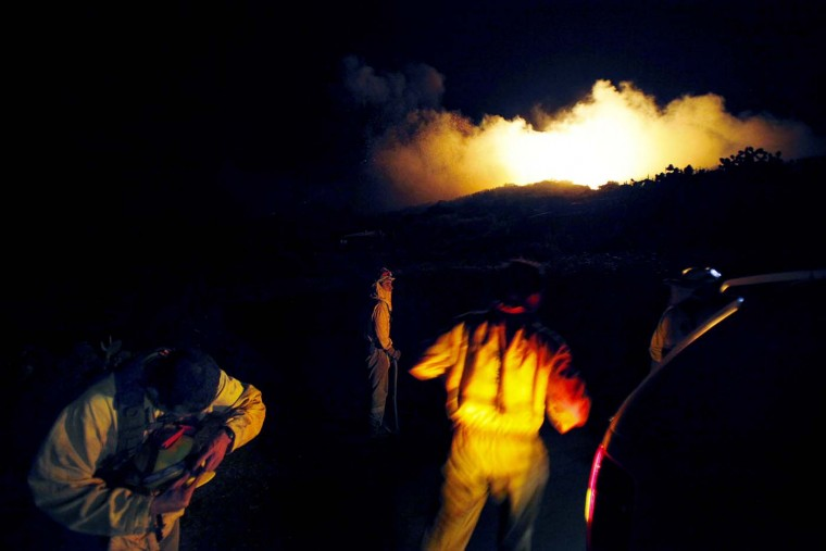 Emergency services personnel arrive as smoke rises from a wildfire raging on the outskirts of the town of Mazo on tthe Spanish Canary island of La Palma early on August 5, 2012. (Desiree Matin/AFP/Getty Images)