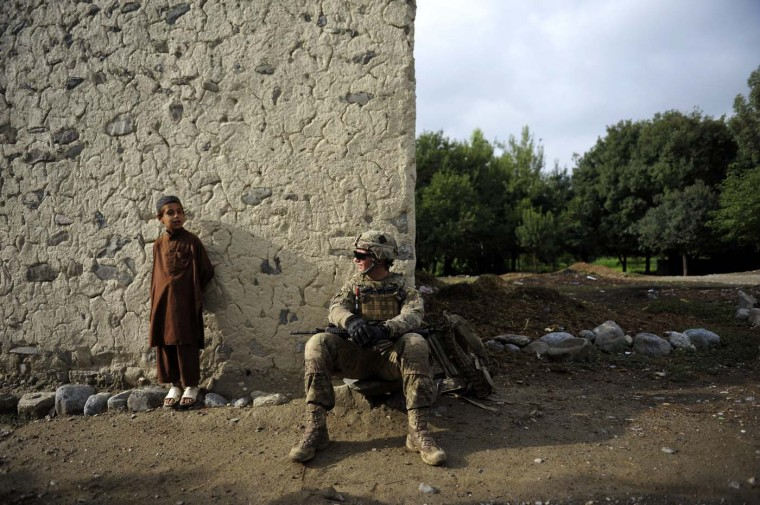 A U.S. soldier from Apache team, Task force Geronimo interacts with an Afghan child in the village of Karizona, Sabari District in Khost Province on August 5, 2012. NATO has some 130,000 US-led troops in Afghanistan helping Karzai's government fight the insurgency, but they will pull out by the end of 2014, handing responsibility for security to Afghan forces. (Jose Cabezas/AFP/Getty Images)