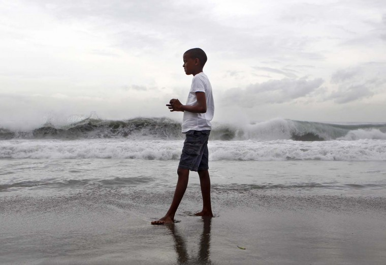 TOPSHOTS A boy watches the high waves caused by Storm Ernesto along the south coast in Santo Domingo on August 4, 2012. (Erika Santelic/AFP/Getty Images)