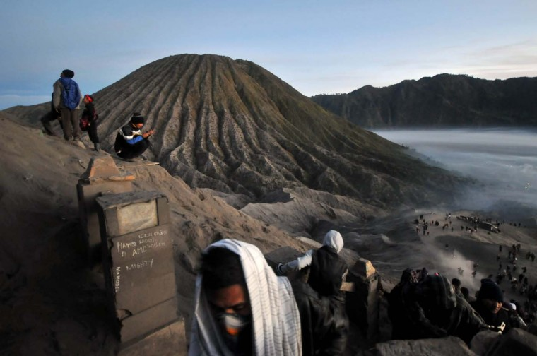 This photograph taken on August 4, 2012 shows worshippers climbing the crater of Mount Bromo volcano in East Java province bearing their offerings during the annual Kasada Festival held by Indonesia's Hindu minority belonging to the Tennger tribe. Hundreds of worshippers make offerings of food and livestock at the active volcano's crater as an ancient act of sacrifice to bring prosperity to their family and community. (Kimikimi/AFP/Getty Images)