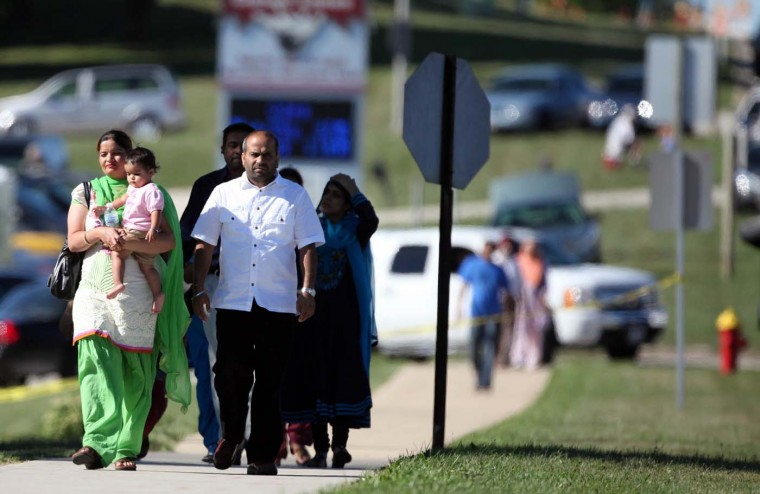 OAK CREEK, WI - AUGUST 5: People walk near the Sikh Temple of Wisconsin where a gunman fired upon people at a service on August, 5, 2012 Oak Creek, Wisconsin. At least six people were killed when a shooter, who was later shot dead by a police officer, opened fire on congregants in the Milwaukee suburb. (Tasos Katopdois/AFP/Getty Images)