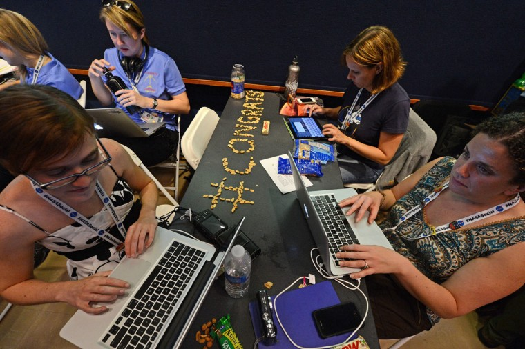 August 5, 2012: Bloggers, Twitter and Facebook social media users type on their computers at a desk with the hastag #CONGRATS written on it using peanuts after the Mars Rover Curiosity successfully landed on the surface of the Red Planet at the Jet Propulsion Laboratory in Pasadena, California. (Robyn Beck/AFP/Getty Images)