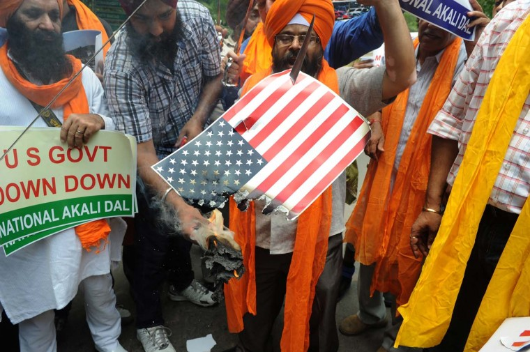 AUGUST 6: Activists of the National Akali Dal burn the U.S. flag as they shout anti-US slogans during a protest in New Delhi on August 6, 2012, after a gunman in the U.S. shot worshippers at a suburban Sikh temple in Wisconsin. (Hussain Sajjad/AFP/Getty Images)