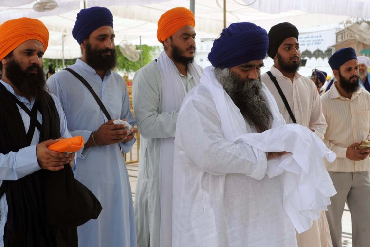AUGUST 6: Damdami Taksal chief Harnam Singh Dhumma (3rd R) leads followers as they offer prayers to Sikhs killed at a temple in the U.S., at the Golden temple in Amritsar on August 6, 2012. (Narinder Nanu/AFP/Getty Images)