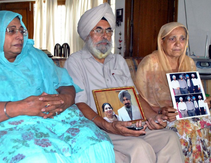 AUGUST 6: Siblings (L to R) Harinder Kaur Rakhra, Amarjit Singh Kaleka, and Jaswinder Kaur pose with family photographs of their brother Satwant Singh Kaleka, president of the gurdwara (temple) in the U.S. who was killed when a gunman shot worshippers in the temple, in Patiala on August 6, 2012. (Stringer/AFP/Getty Images)
