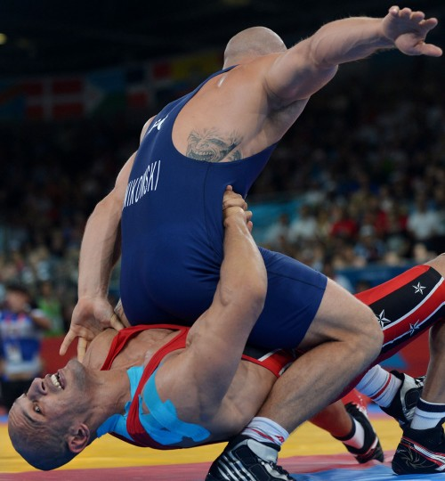 Egypt's Karam Mohamed Gaber Ebrahim (red) fights Poland's Damian Janiskowski (blue) during the semi-final of 84 kg men's Greco-Roman at the London 2012 Olympic Games in London on August 6, 2012. (Adek Berry/AFP/Getty Images)