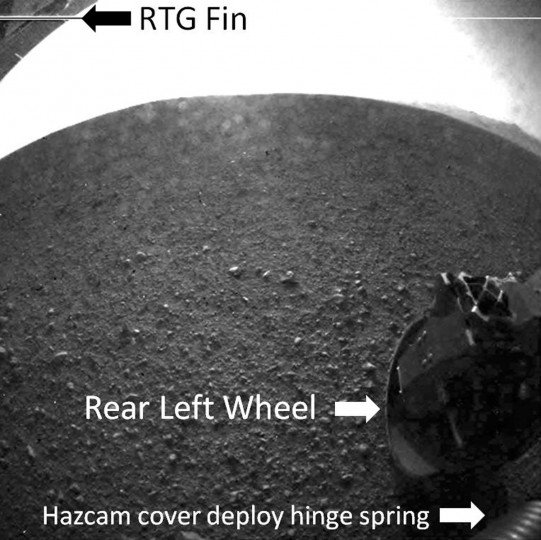 "August 6, 2012: This image, provided by NASA, shows a labeled version of one of the first images taken by a rear Hazard-Avoidance camera on NASA's Curiosity rover, which landed on Mars the evening of Aug. 5 PDT. The image shows a fin on the radioisotope thermoelectric generator (the rover's power source), the rear left wheel and a spring that released the dust cover on the Hazard-Avoidance camera. It was taken through a ""fisheye"" wide-angle lens. (NASA/JPL-Caltech/HO/AFP/GettyImages)"