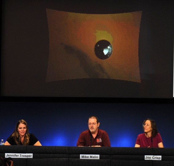 August 6, 2012: Mars Descent Imager principal investigator Michael Malin (C), Mars Science Laboratory (MSL) mission director Jennifer Trosper (L) and MSL deputy project scientist Joy Crisp discuss an image sent by the Mars Rover Curiosity showing the heat shield falling away from the Rover (not in photo) as it descents toward the Martian surface at a press conference at NASA's Jet Propulsion Laboratory in Pasadena, California. (Robyn Beck/AFP/Getty Images)