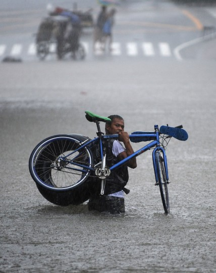 A man carries his bicycle through a flooded street in Quezon City, suburban Manila. Half of Manila was under water and 250,000 people fled their homes on August 7 as torrential rain paralysed the city, sweeping away houses, stranding residents on rooftops and triggering a landslide. (Ted Aljibe/AFP/Getty Images)