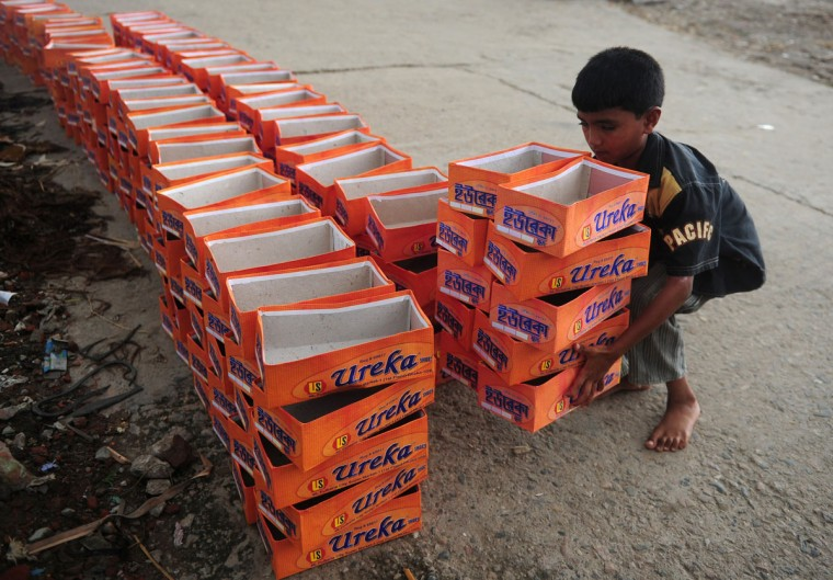A Bangladeshi child lifts shoe boxes at a factory in Dhaka. Bangladesh is one of the poorest nations with 40 percent of its 144 million people living on less than one dollar a day. (Munir uz Zaman/AFP/Getty Images)