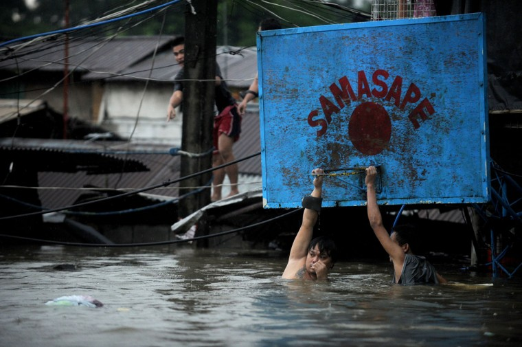 Two men hang onto a basketball hoop in floodwaters after a river overflowed in Manila caused by torrential rains across the capital. At least five people were killed and seven were missing as torrential rains brought the Philippine capital to a standstill, with floodwaters covering half the sprawling city, officials said. (Noel Celis/AFP/Getty Images)