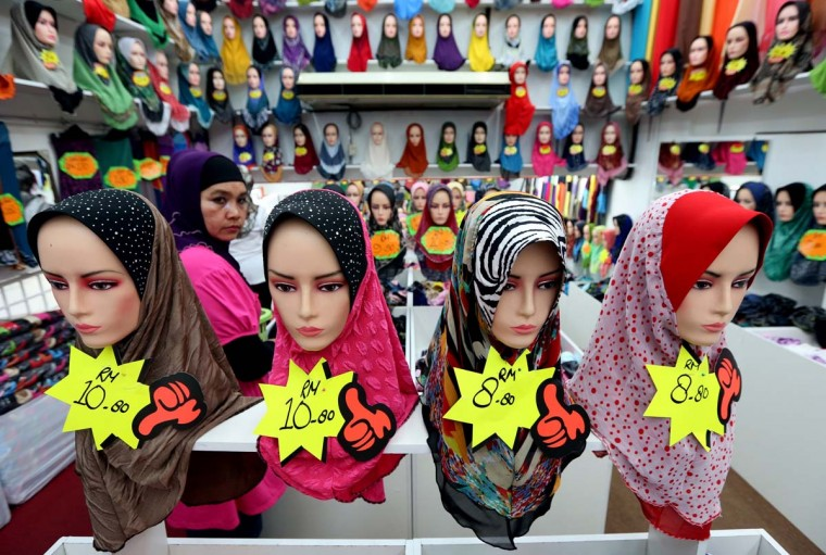 A woman browses a shop selling headscarves ahead of the upcoming Muslim Eid al-Fitr festival in Kuala Lumpur. Muslims throughout the world will celebrate the Eid al-Fitr festival after the holy month of Ramadan in which they refrain from sexual activities, eating and drinking from sunrise until sunset. (Mohd Rasfan/Getty images)