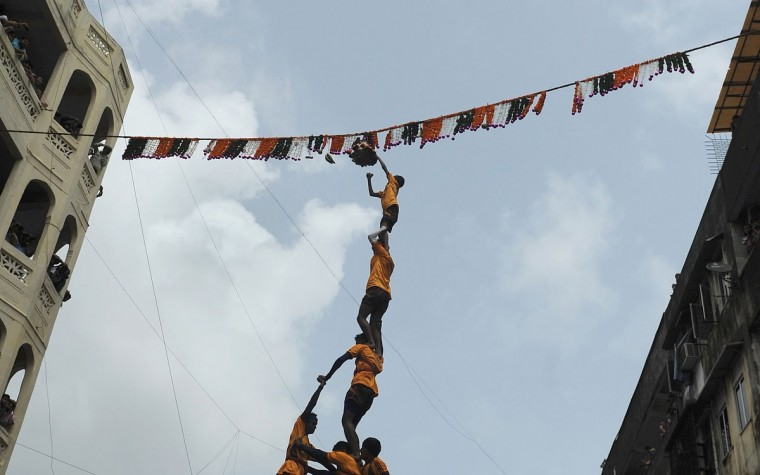 Indian Hindu devotees form a human pyramid to break the dahi-handi, curd-pot, suspended in the air during celebrations of Janmashtami, which marks the birth of Hindu God Lord Krishna, in Mumbai. Hindu men and boys receive prize money by constructing a human pyramid till it is tall enough to enable the topmost person to reach the pot and claim the contents after breaking it. (Punit Paranjpe/AFP/Getty Images)