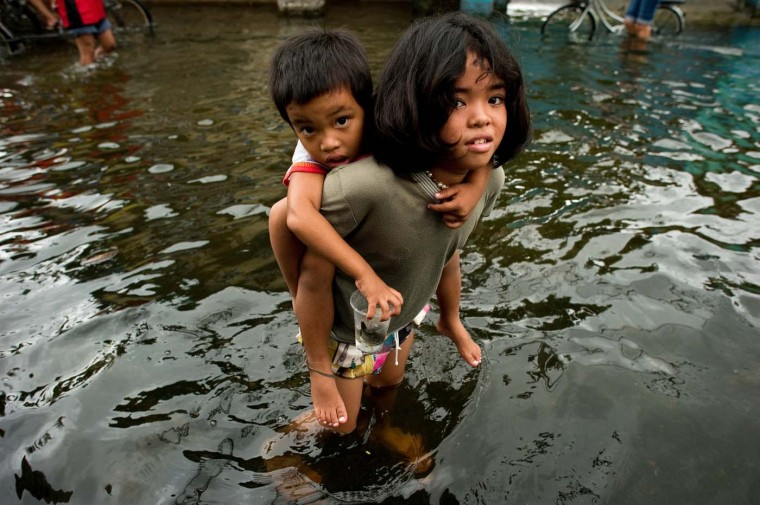 A girl hold a boy on her back to help him cross the floodwaters in a street in Valenzuela, on the outskirt of Manila on August 13, 2012. Philippine authorities warned an intensifying storm could bring more misery to the flood-battered capital and surrounding areas, where nearly half a million were in evacuation centers. (Nicolas Asfouri/AFP/Getty Images)