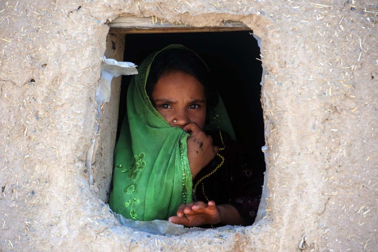 An Afghan girl looks on as she works in