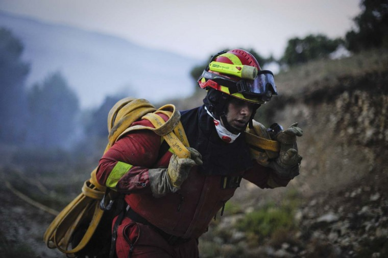 A member of the Spanish Emergency Army carries a fire hose in Torre de Macanes during a forest fire near Alicante on August 13, 2012. Emergency teams battled through the night to quell the flames in the pine forests around Torre de les Macanes north of Alicante, which claimed their first victim, a member of the firefighting team, on August 12, 2012. (Pedro Armestre/AFP/Getty Images)