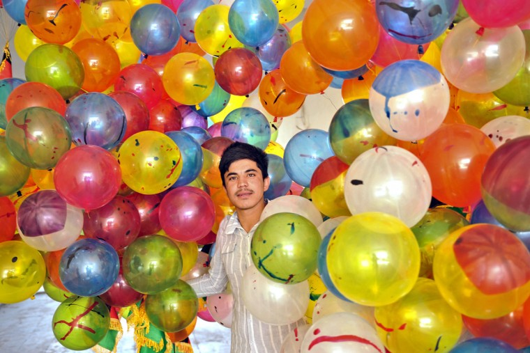 An Afghan young man carries balloons during a welcoming ceremony for the country's athletes at Kabul stadium following the completion of the 2012 London Olympic Games. The six-strong Afghanistan Olympic team returned to Kabul, bringing home a bronze medal in Taekwondo. (Massoud Hossaini/AFP/Getty Images)