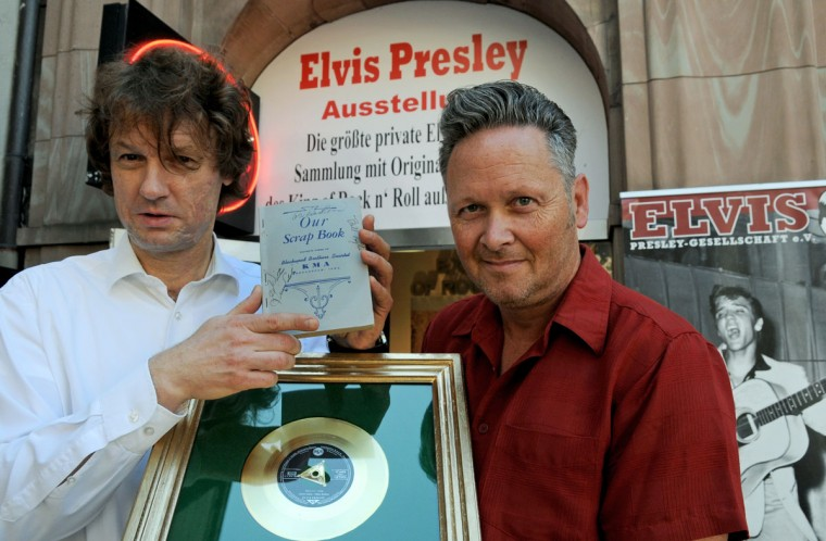 "August 15, 2012: German collectors Torsten Meck (L) and Andreas Schrãer (R) display the latest addition of memorabilia to their Elvis Presley Museum, a song book and a Golden Record award for ""Hound Dog,"" in Duesseldorf, western Germany. The museum hosts the biggest private Elvis Presley collection outside the US. Presley died 35 years ago on August 16, 1977. (Horst Ossinger/AFP/Getty Images)"