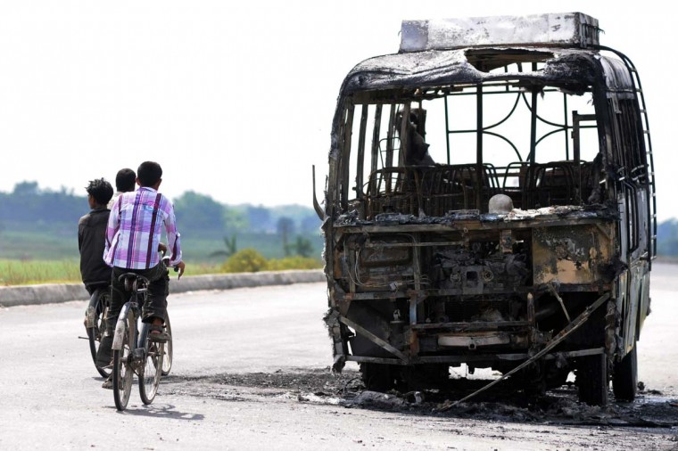 Cyclists ride past the burnt-out wreckage of a bus, which was set on fire by angry rioters, at Udiana village in Kamrup district, some 50 kms from Guwahati in India's Assam state. An angry mob torched a bus and burnt a road bridge in a restive region of northeast India as violence blamed for a spike in inter-religious tension across the country flared again. (Getty Images)