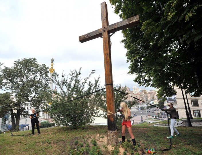 UKRAINE - AUGUST 17: Activists of the Ukrainian feminist group Femen use a chainsaw to cut down an Orthodox cross, erected to the memory of victims of the political repression in Kiev on August 17, 2012, in support of Russian punk group Pussy Riot. (Genya Savilov/AFP/Getty Images)