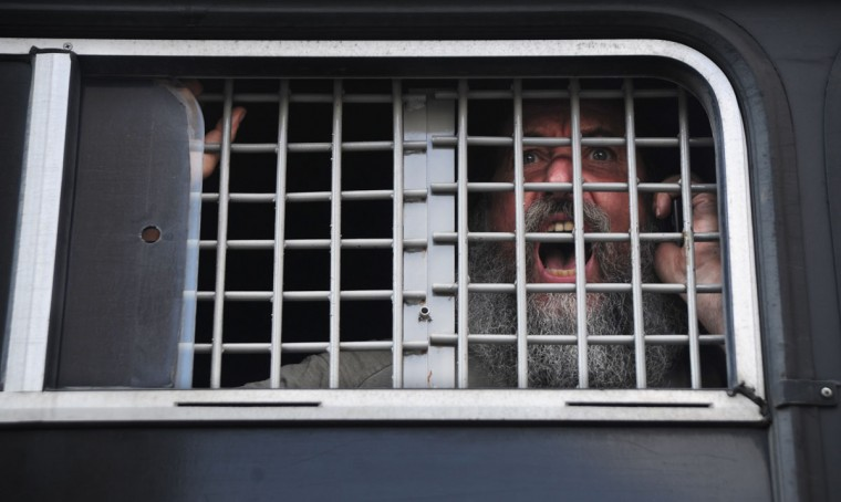 "MOSCOW, RUSSIA - AUGUST 17: A supporter of all-girl punk band ""Pussy Riot"" shouts inside of a police car as he was detained near a court building in Moscow on Agust 17, 2012. (Andrey Smirnov/AFP/Getty Images)"