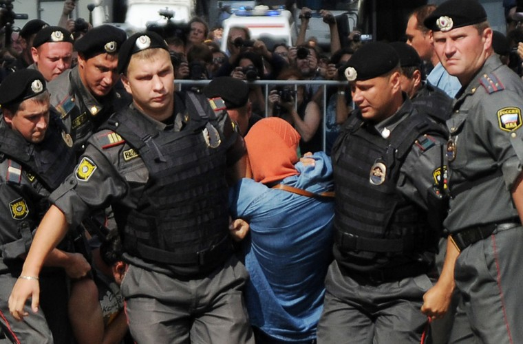 "MOSCOW, RUSSIA - AUGUST 17: Russian riot policemen detain a supporter of all-girl punk band ""Pussy Riot"" near a court building in Moscow on Agust 17, 2012. (Andrey Smirnov/AFP/Getty Images)"