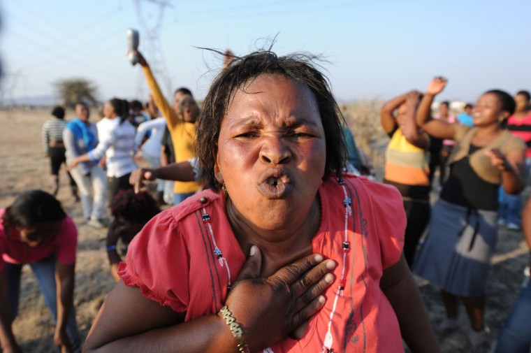 Women sing, dance and protest at the scene where 34 people died after police opened fire on striking mineworkers in Marikana. The workers at the Marikana mine were on a week-long wildcat strike demanding a tripling of their wages from the current 4,000 rand ($486) a month. South African police insisted today they only fired in self-defense during the clash, the deadliest protest since the end of apartheid. (STR/AFP/Getty Images)