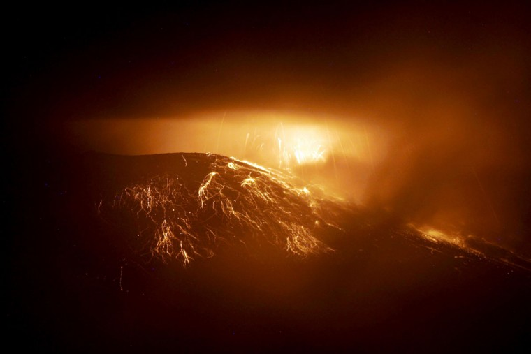 View of the Tungurahua Volcano spewing incandescent rocks and lava, from Juive, Ecuador, on August 19, 2012. A reactivation of the eruptive process of the Tungurahua volcano, forced authorities to increase from yellow to orange the alert in the surrounding areas. (Carlos Campana/AFP/Getty Images)