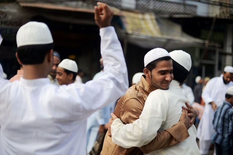 Indian Muslims embrace after offering Eid al-Fitr prayers near the Jama Masjid Mosque in the old quarters of New Delhi on August 20, 2012. (Roberto Schmidt/AFP/Getty Images)