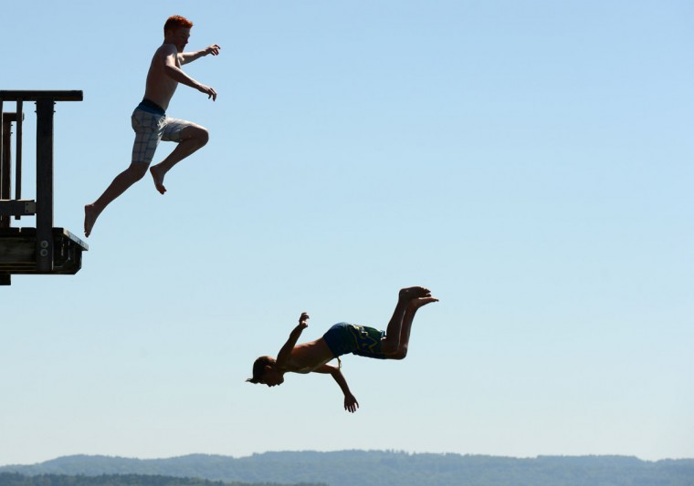 Boys jump from the diving platform of the lido at the lake Ammersee near the small village Utting, southern Germany, on August 20, 2012. Many people enjoy the sunny hot weather with temperatures by 30 degrees near the seaside of the Ammersee. Temperatures in the German capital reached 30 degrees Celsius. (Christof Stache/AFP/Getty Images)