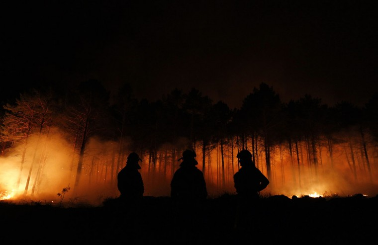 Fire fighters work at the site of a wildfire in Tabuyo del Monte, near Leon. Numerous wildfires have broken out across Spain in the sweltering heat in recent weeks, an extra headache for authorities struggling to get the country out of its financial crisis and recession. (Cesar Manso/AFP/Getty Images)