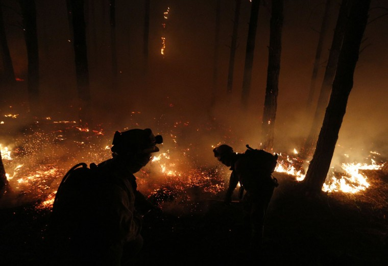 Fire fighters work at the site of a wildfire in Tabuyo del Monte, near Leon. (Cesar Manso/AFP/Getty Images)