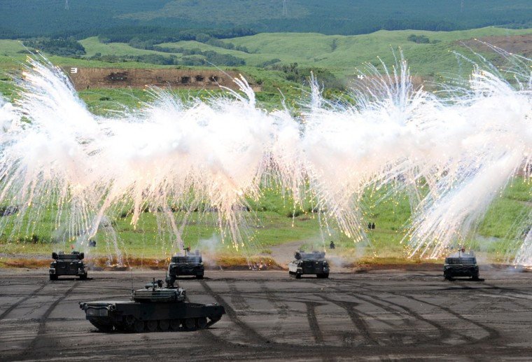 Japanese Ground Self-Defense Forces tanks move amongst an umbrella of barrage during an annual live fire exercise at the Higashi-Fuji firing range in Gotemba, at the foot of Mt. Fuji in Shizuoka prefecture. The annual drill involves some 2,400 personnel, 80 tanks and armoured vehicles and 30 aircraft and helicopters. (Yoshikazu Tsuno/AFP/Getty Images)
