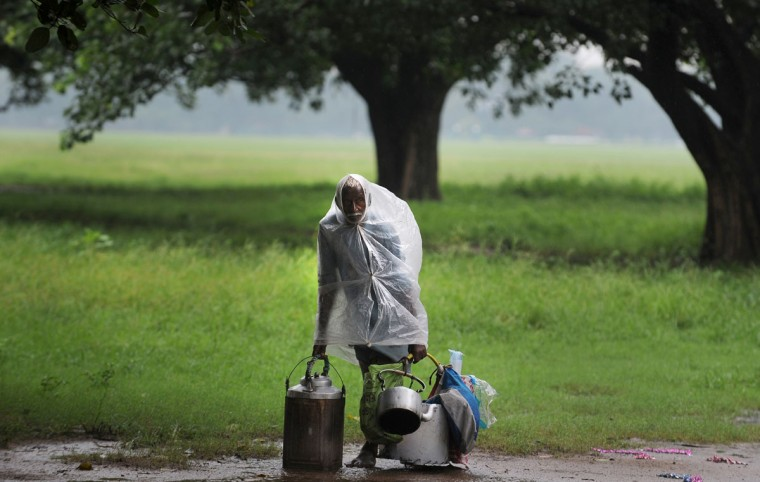 An Indian tea-vendor, covered with a plastic sheet for protection from rain, waits for customers in Kolkata. Even with increased rain, according to Indian Meteorological Department, the overall rain deficit for the country is 15 percent. (Dibyangshu Sarkar/AFP/Getty Images)