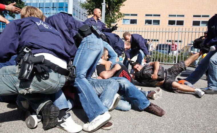 Police arrest a group asylum seekers from Iraq who have exhausted all their rights to appeal at the Immigration and Naturalisation Service in Zwolle, the Netherlands. The Iraqis were calling for their asylum application to be re-examined. (Mischa Rapmund/Getty Images)