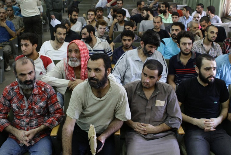 Syrian prisoners, who had been arrested for their involvement in anti-regime protests, wait to be released in Damascus on August 27, 2012. The official SANA agency reported that authorities released 378 people detained for their participation in street protests, adding that those freed were never involved in acts of violence. (Louai Beshara/AFP/Getty Image)
