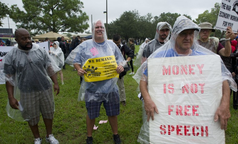Anti-GOP protesters stand in the rain during a protest rally in downtown Tampa, Florida August 27, 2012. Due to incoming severe weather and possible hurricane conditions expected to hit the state by Monday, the Republicans have decided to cut short their National Convention by one day. (Mladen Antonov/AFP/Getty Images)