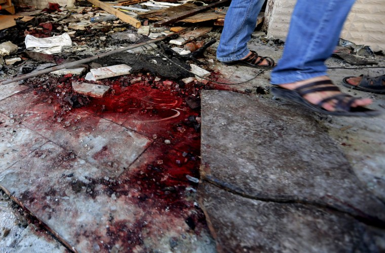 A Syrian man walks past a blood stain at the site of a car bomb in the mainly Druze and Christian suburb of Jaramana on the southeastern outskirts of the Syrian capital. (Joseph Eid/AFP/Getty Images)