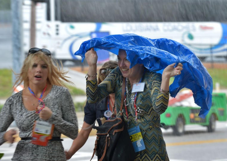 Delegates run for shelter from sudden rain near the Tampa Bay Times Forum in Tampa, Florida during the Republican National Convention. Mitt Romney and his wife Ann arrived in Tampa for the first full day of a gala Republican convention to bless him as the party's candidate to run against President Barack Obama. (Jewel Samad/AFP/Getty Images)