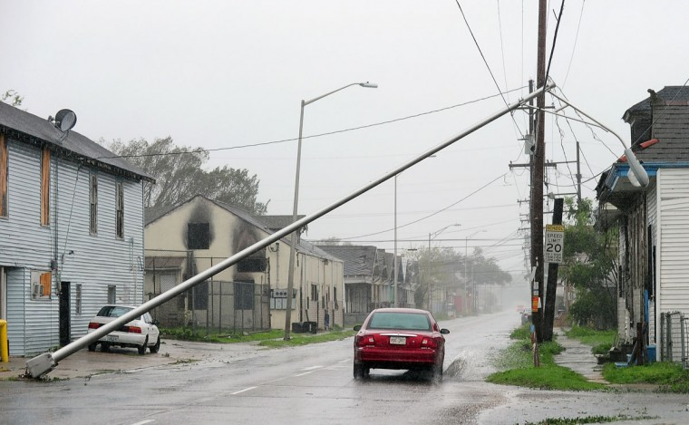 A car drives beneath a fallen streetlight along deserted streets in New Orleans, Louisiana on August 29, 2012 as Hurricane Isaac battered the city and surrounding region, seven years to the day after Katrina devastated the city. (Frederic J. Brown/AFP/Getty Images)