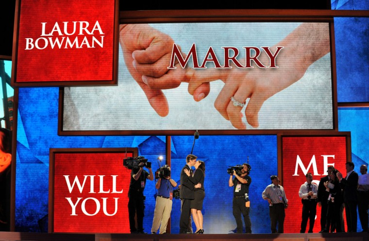 Bradley Thompson (L) and Laura Bowman (R) hug after Thompson proposed to Bowman on the stage as large background screens show his question at the Tampa Bay Times Forum in Tampa, Florida, on August 29, 2012 during the Republican National Convention. Thompson is production manager and Bowman is a production coordinator for the convention. (Stan Honda/AFP/Getty Images)