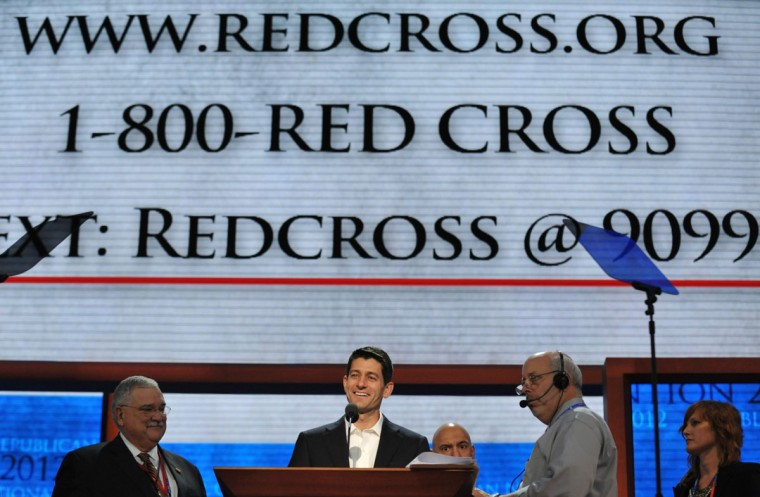 GOP Vice presidential nominee Paul Ryan (C) stands underneath the giant screen displaying the call number for the Red Cross during a sound check at the Tampa Bay Times Forum in Tampa, Florida, on August 29, 2012 before the day's Republican National Convention (RNC) events. (Stan Honda/AFP/Getty Images)
