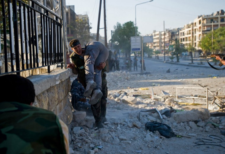 An opposition fighter carries the body of his brother and comrade, who was killed during conflict in Aleppo, Syria, amid heavy street fighting. (Zac Baillie/AFP/Getty Images)