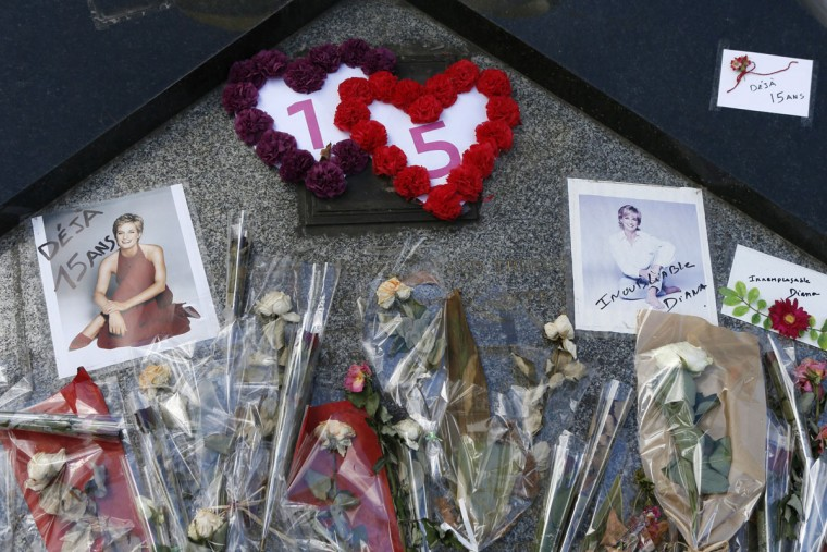 """Pictures and flowers have been laid down under the """"Flame of Freedom"""" statue at the Pont de l'Alma underpass where Lady Diana died, on the eve of the 15th anniversary of her death. (Patrick Kovarik/AFP/Getty Images)"""