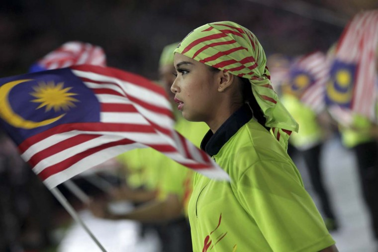 """Malaysian students perform with national flags during a rally to celebrate country's 55th Independence Day in Bukit Jalil Stadium, some 20 kilometres south of Kuala Lumpur, on August 31, 2012. Malaysians gathered for the """"Perhimpunan Janji Ditepati"""" (Promises Fulfilled Gathering) in celebrating the country's 55th Independence Day. (Mohd Rasfan/Getty Images)"""