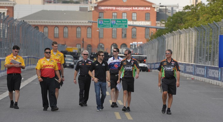 Aug. 31: Andretti Autosport team members, including driver James Hinchcliffe (black shirt, jeans, hand near pocket) walk the track looking for changes along the warehouse by pit lane. (Gene Sweeney Jr./Baltimore Sun)