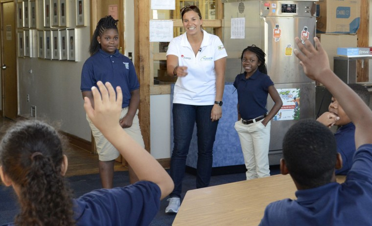 Aug. 29: Simona De Silvestro, (white shirt) a race car driver who will race in this weekend's Grand Prix, talks to Living Classrooms Foundation sixth grade Crossroads School students about IndyCar Racing and her car. Standing next to her at left is Brea Baylor; at right is Nasia Dismel Students are from Crossroads, a public charter middle school operated by Living Classrooms. (Algerina Perna/Baltimore Sun)