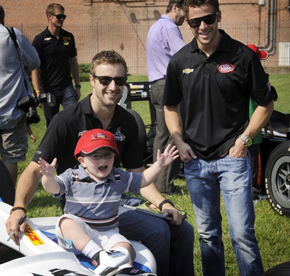 Aug. 30: Four year old Matthew Merryman of Frederick reacts with glee as he sits on an Indycar fender. Grand Prix drivers James Hinchcliffe, left, and Marco Andretti, right, were some of the drivers from this weekend's race who visited Kennedy Krieger School this morning. (Barbara Haddock Taylor/Baltimore Sun)