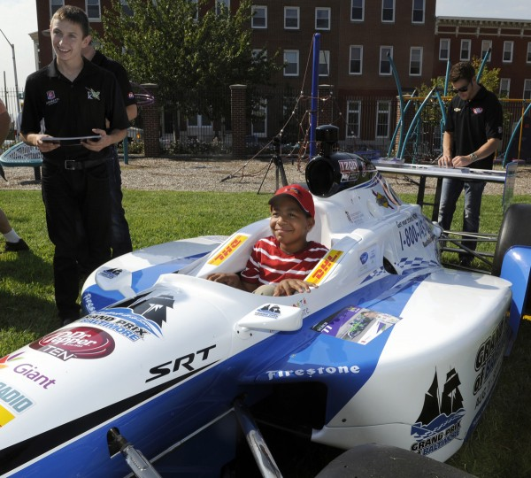 Aug. 30: Isaiah Downs, 9, sits in an Indy car on the grounds of Kennedy Krieger School. Grand Prix driver Zach Veach is on left. Several drivers, along with a couple of cars from this weekend's race visited Kennedy Krieger School this morning. (Barbara Haddock Taylor/Baltimore Sun)