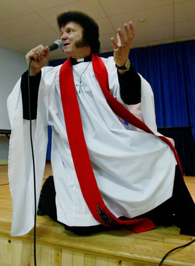 "January 5, 2003: Reverand Dorian Baxter strikes an Elvis pose as he sings a gospel song during a service at the Royal Canadian Legion in Newmarket, Ontario. In the Christ the King Graceland Independent Anglican Church of Canada, ""Rockin' Reverend'' Dorian Baxter, who is equal parts entertainer, activist and preacher, does it his way, singing Elvis favorites with a Christian twist. (Kevin Frayer/CP/AP Photo/)"